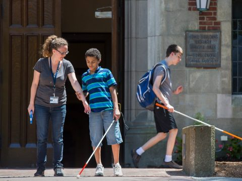 photo of blind student with white cane being shown orientation and mobility.
