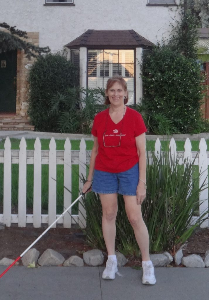 Picture of Shell wearing a red shirt, shorts and holding a white cane in fron of her childhool home.