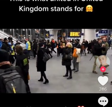 Crowd of people coming together in an airport to sing Lean On Me.